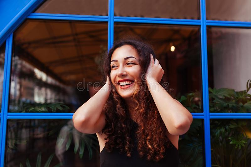 Happy young woman laughing against blue window. Outdoor portrait of beautiful teen girl smiling royalty free stock photos