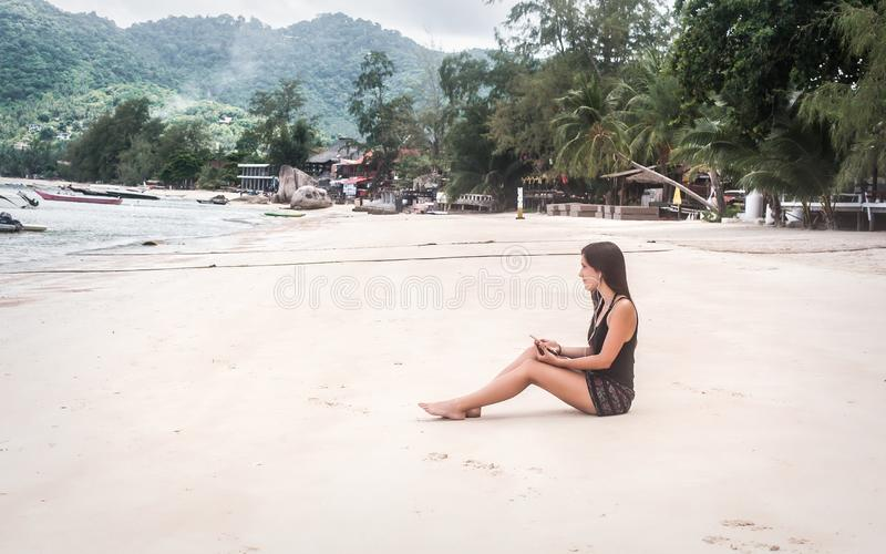 Happy young woman listening music on smartphone, enjoying on beach. Tropical travel holidays royalty free stock photography