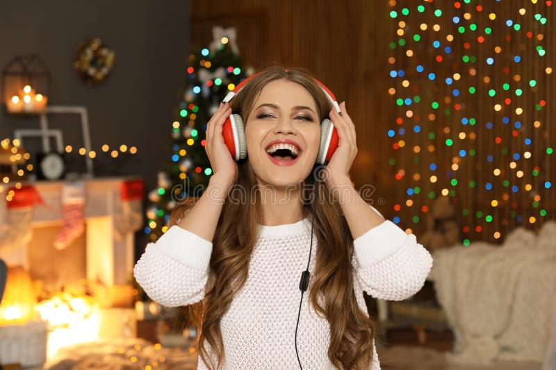 Happy young woman listening to Christmas music royalty free stock photography