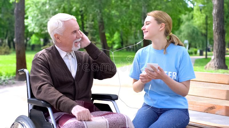 Happy young woman listening to music with old disabled man, supporting patient royalty free stock photography