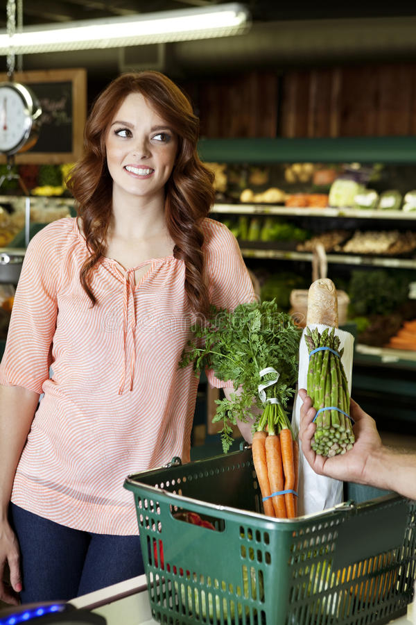 Download Happy Young Woman Looking Away While Hand Holding Vegetable In Supermarket Stock Image - Image: 29674335