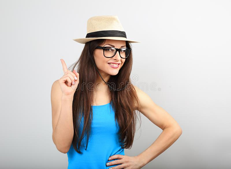 Happy young woman looking in fashion glasses and straw hat have a great idea. About vacation on blue color background royalty free stock photos