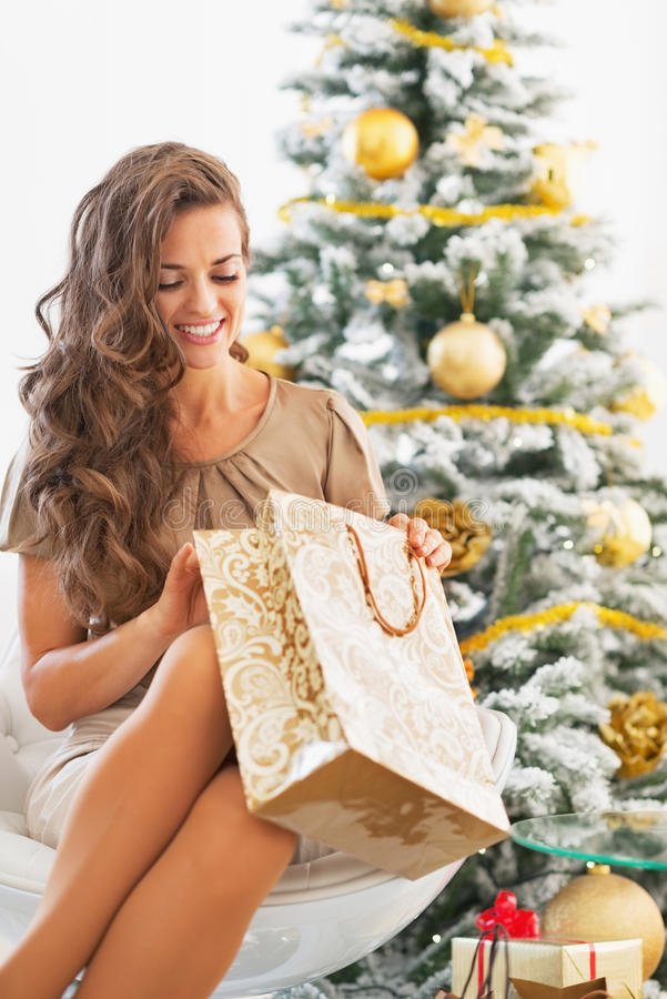 Happy young woman looking into shopping bag near christmas tree. In living room stock photography