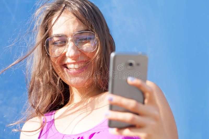 Happy young woman looking at smartphone stock photo