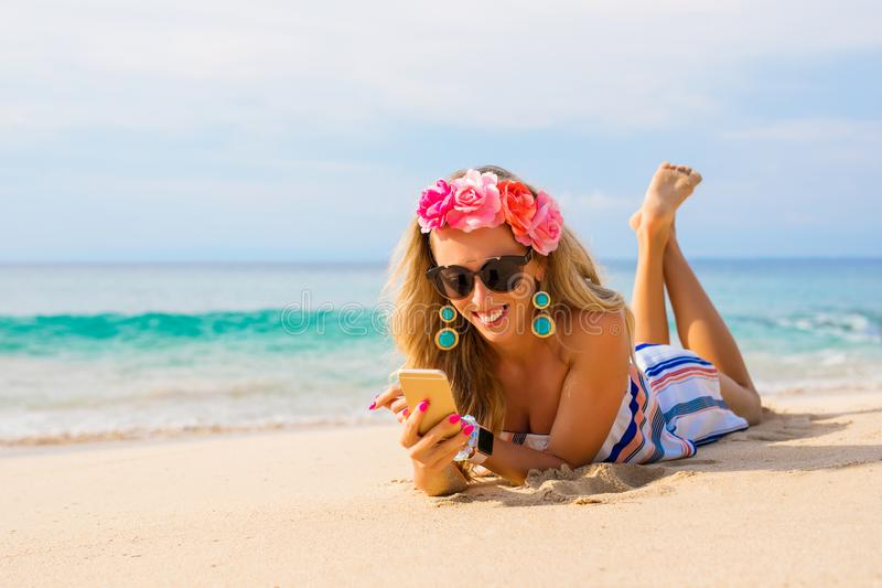 Happy young woman lying on the beach in sand and using mobile phone stock images