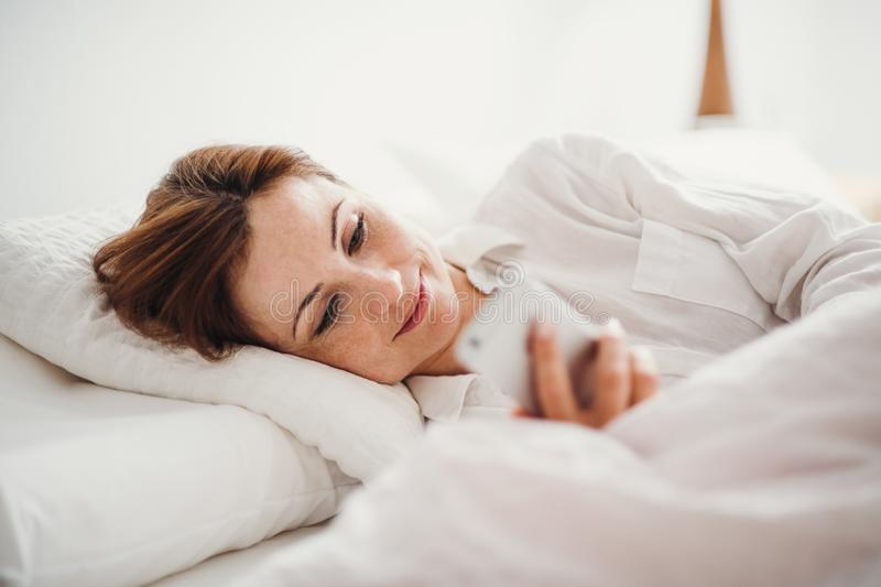 A young woman lying in bed indoors in the morning in a bedroom, using smartphone. royalty free stock photos