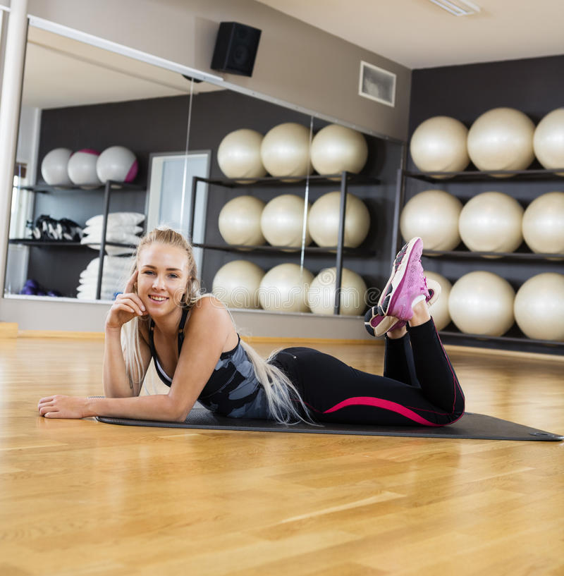 Happy Young Woman Lying On Exercise Mat In Gym royalty free stock photo