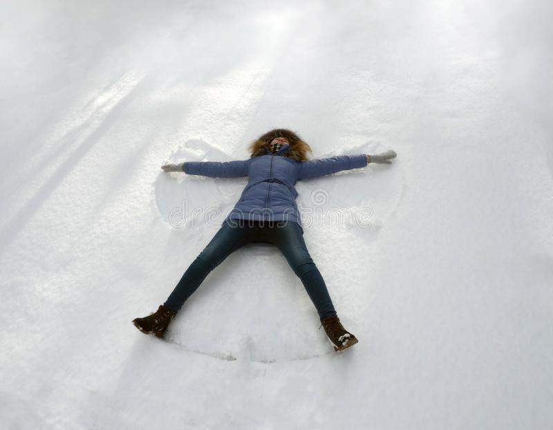 Happy young woman lying on snow fur in wintertime. stock photos