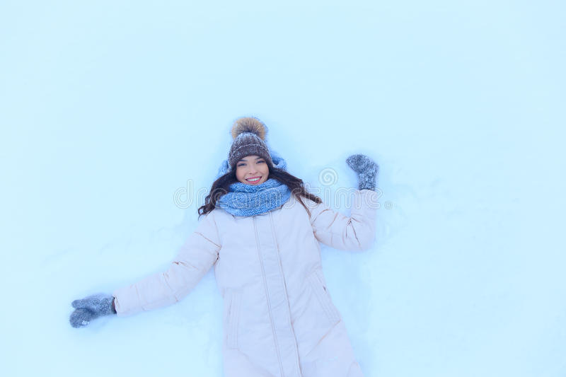 Happy young woman lying on snow in winter royalty free stock image