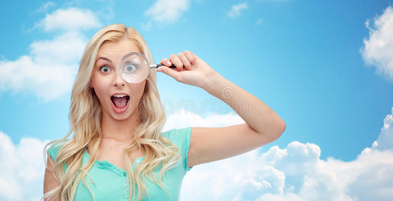Happy young woman with magnifying glass stock photo