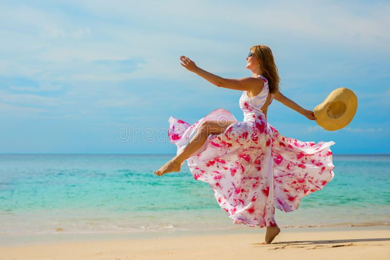 Happy woman making a big step forward on the beach stock image