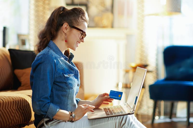 Happy young woman making online purchases on laptop royalty free stock photography