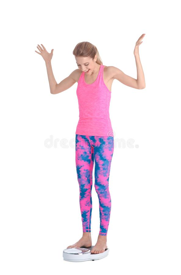 Happy young woman measuring weight using scales on white background. Weight loss motivation stock image