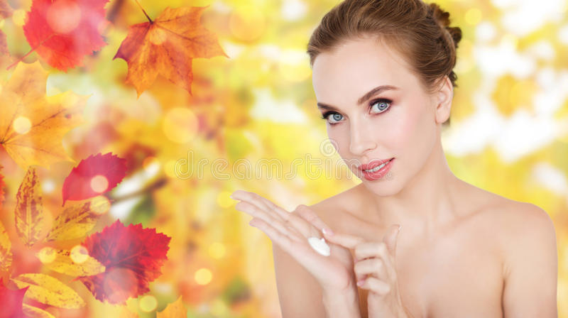 Happy young woman with moisturizing cream on hand stock images