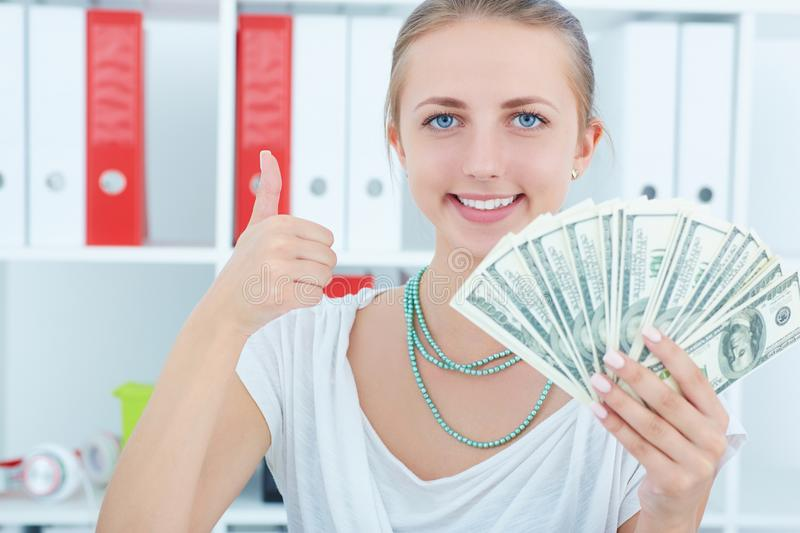 Happy young Caucasian woman with money. Saving account concept. stock images