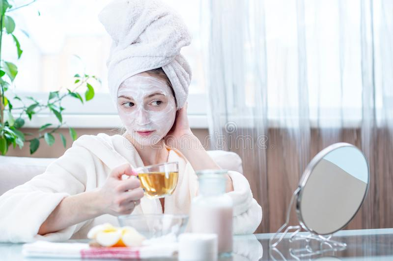 Happy young woman with natural cosmetic mask on her face. Concept skin care and Spa treatments at home royalty free stock photography