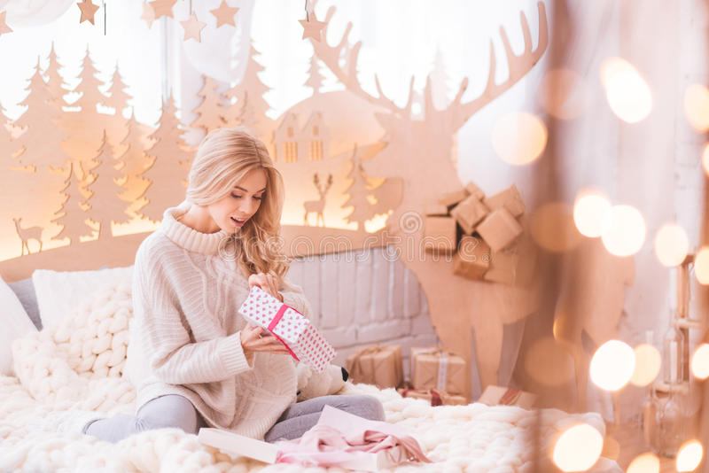 Happy young woman opening her presents royalty free stock photos