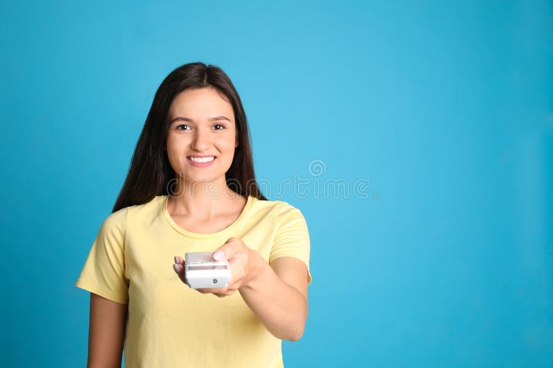 Happy young woman operating air conditioner with remote control on light blue background. Space for stock photography