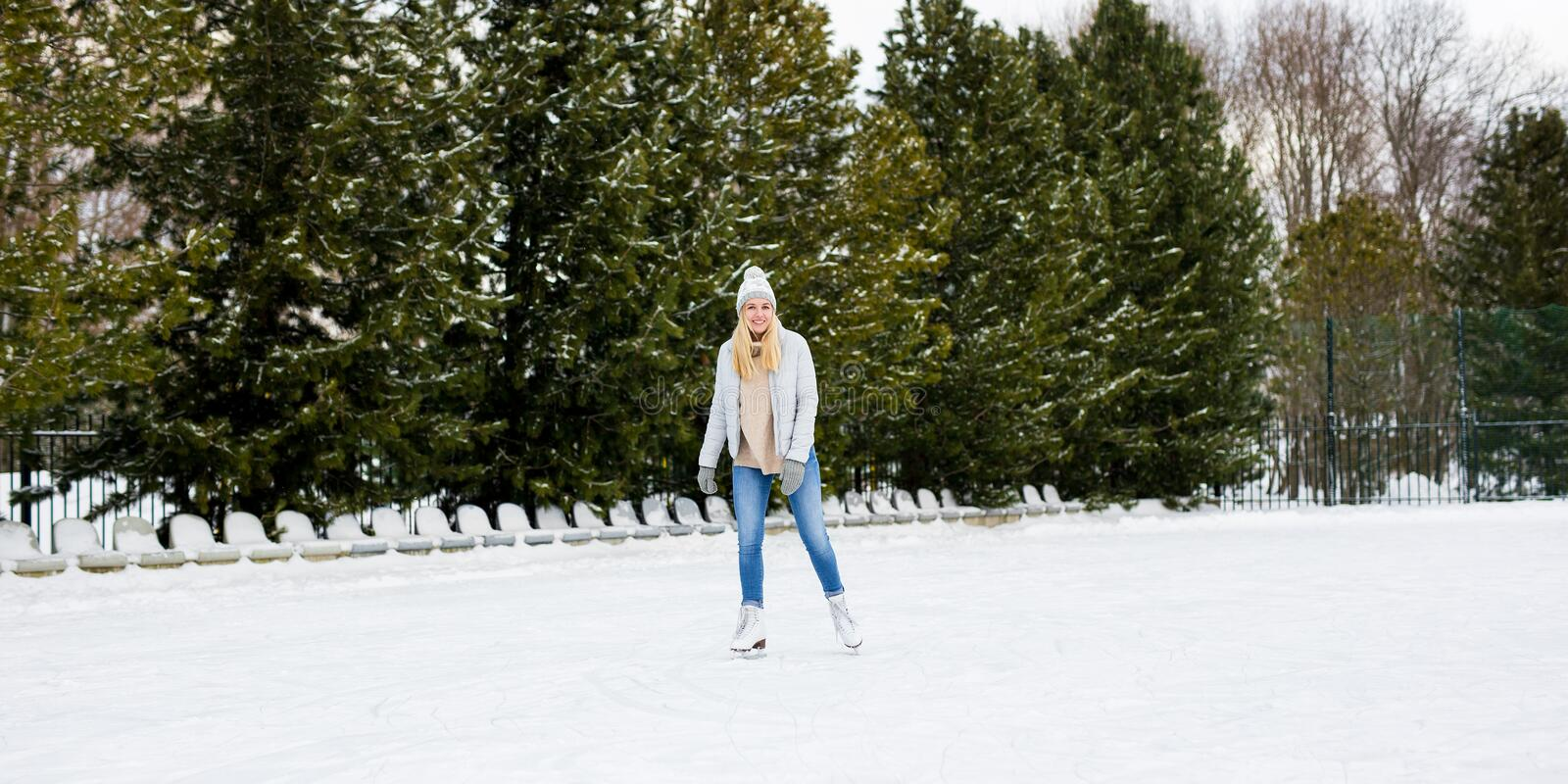 Happy young woman on skating rink. Happy young woman on outdoor skating rink royalty free stock images