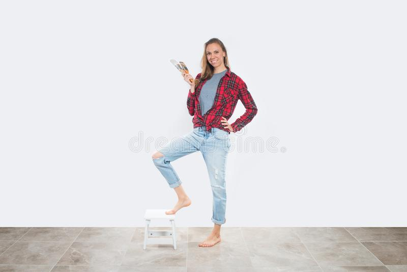 Happy young woman with paintbrushes near empty wall royalty free stock image