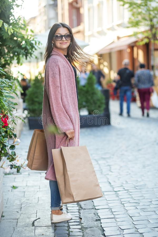 Happy young woman with paper bags in hands. European city. The concept of shopping, gifts, discounts, black bowl and lifestyle stock photo