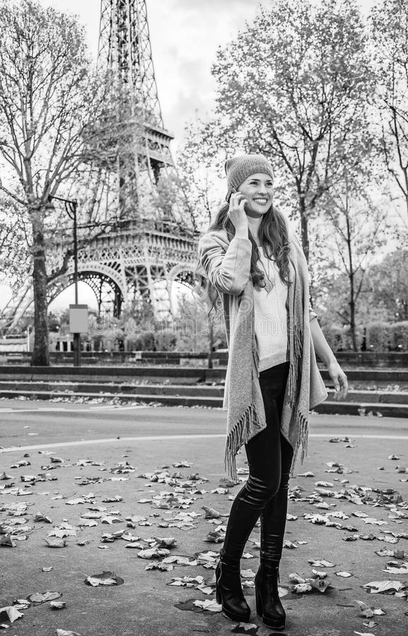 Happy young woman in Paris, France using mobile phone. Autumn getaways in Paris. Full length portrait of happy young woman in Paris, France using a mobile phone royalty free stock photos