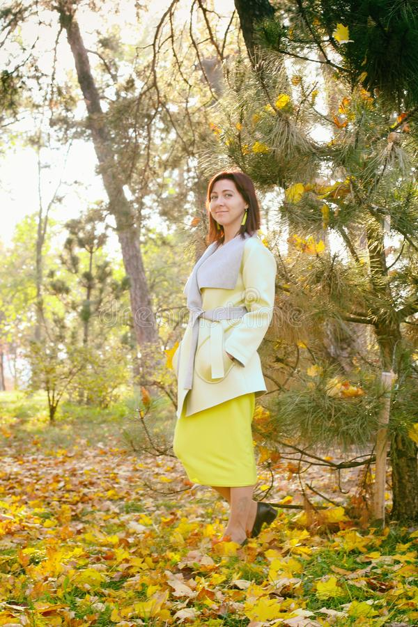 Happy young woman in park on sunny autumn day. Cheerful beautiful girl in green sweater outdoors among yellow leaves on stock images