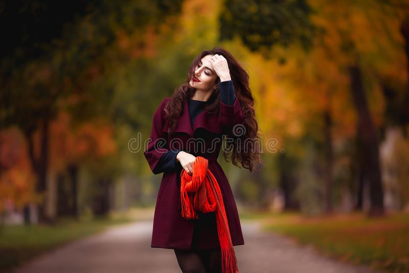 Happy young woman in park on sunny autumn day. Cheerful beautiful girl in red coat and scarf outdoors among yellow royalty free stock photography