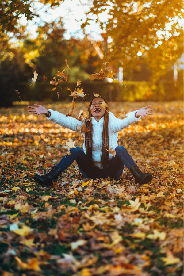 Happy young woman in park on sunny autumn day, laughing, playing leaves. Cheerful beautiful girl in white sweater during autumn se royalty free stock photos