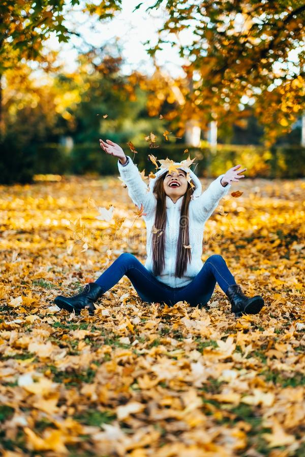 Happy young woman in park on sunny autumn day, laughing, playing leaves. Cheerful beautiful girl in white sweater during autumn se stock images