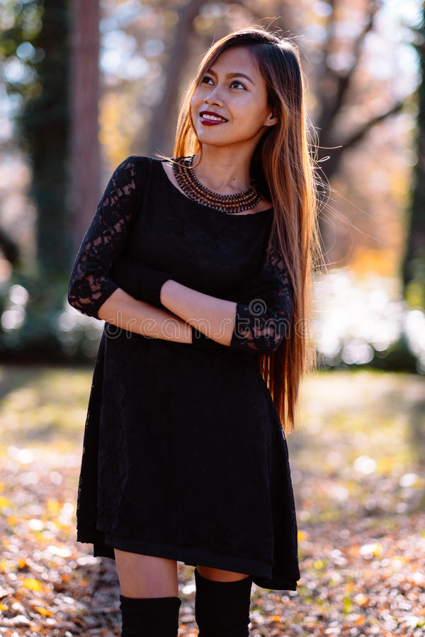 Happy young woman in park on sunny autumn day, smiling. Cheerful beautiful girl in black retro dress autumn fashion style royalty free stock image