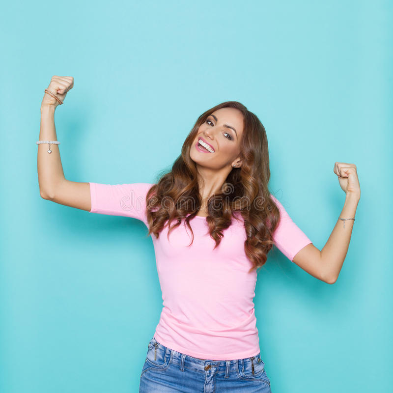 Happy Young Woman In Pastel Colors. Happy beautiful young woman in pastel pink shirt is laughing with arms outstretched. Waist up studio shot on turquoise stock photography