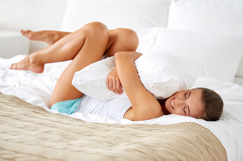 Happy young woman with pillow lying in bed at home royalty free stock photo