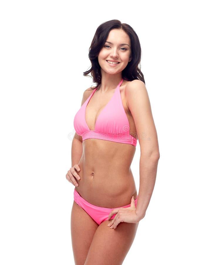 Happy young woman in pink bikini swimsuit. People, fashion, swimwear, summer and beach concept - happy young woman posing in pink bikini swimsuit stock image