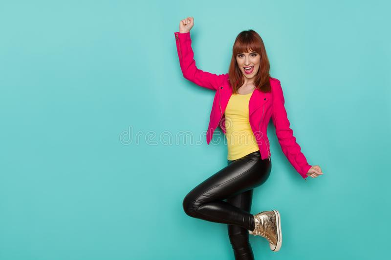 Happy young woman in pink jacket, black leather trousers and gold sneakers is standing on one leg, shouting and rising arm. Three stock photo