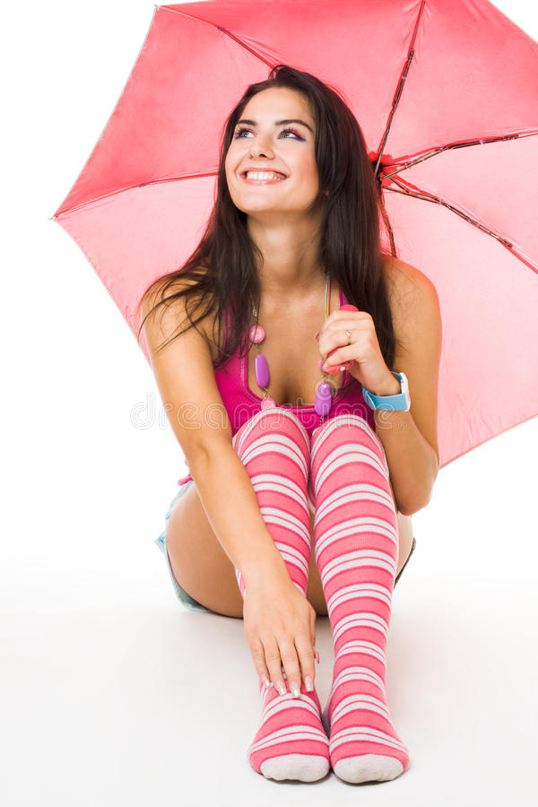 Happy young woman in pink sitting with umbrella. Isolated on white royalty free stock photo