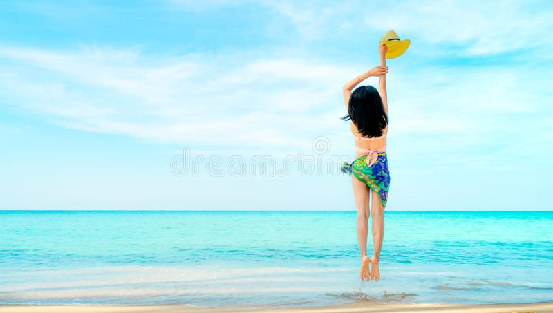 Happy young woman in pink swimwear hand holding hat and jumping at sand beach. Relaxing and enjoying holiday at tropical paradise royalty free stock images