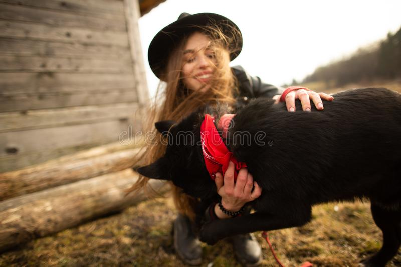 Happy young woman plaing with her black dog Brovko Vivchar in fron of old wooden house royalty free stock photos
