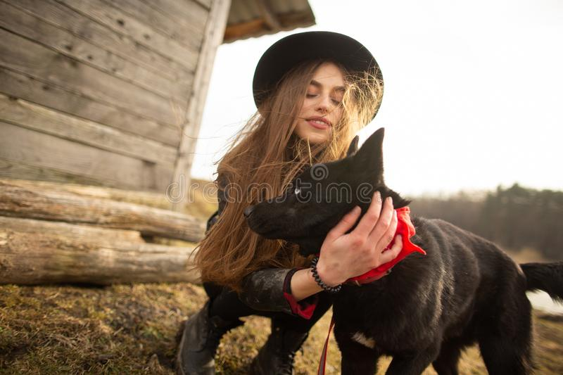 Happy young woman plaing with her black dog Brovko Vivchar in fron of old wooden house stock photos