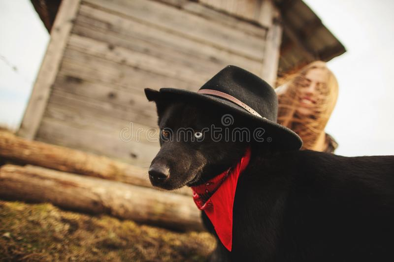 Happy young woman plaing with her black dog in fron of old wooden house. Girl tries a hat to her dog.  royalty free stock images