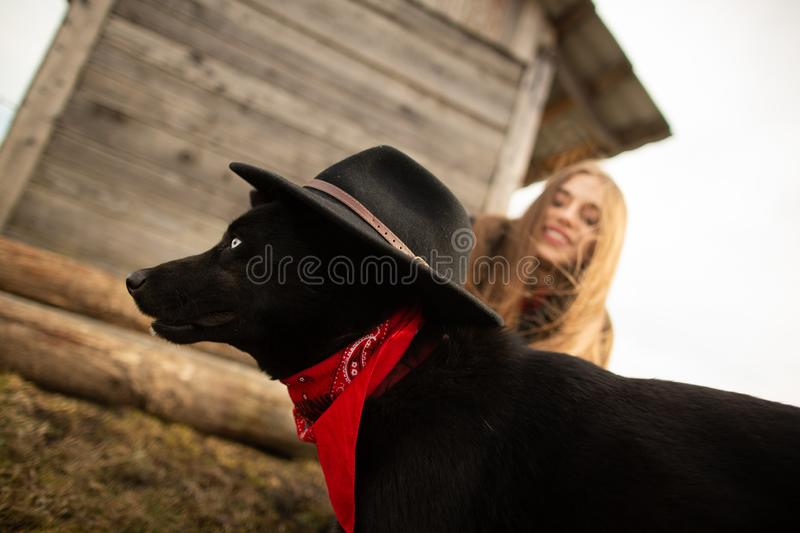 Happy young woman plaing with her black dog in fron of old wooden house. Girl tries a hat to her dog royalty free stock photo
