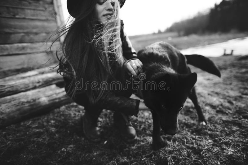 Happy young woman plaing with her black dog in fron of old wooden house. Black and white photo royalty free stock photography