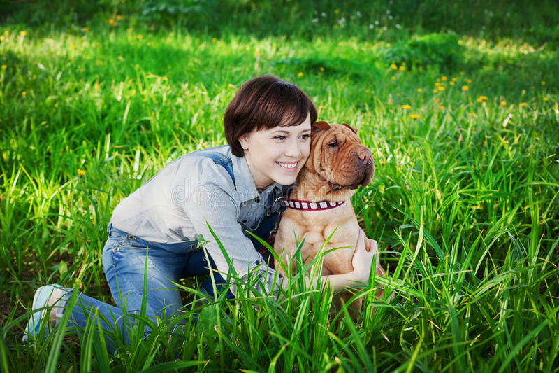 Happy young woman playing with dog Shar Pei in the green grass, true friends forever royalty free stock images