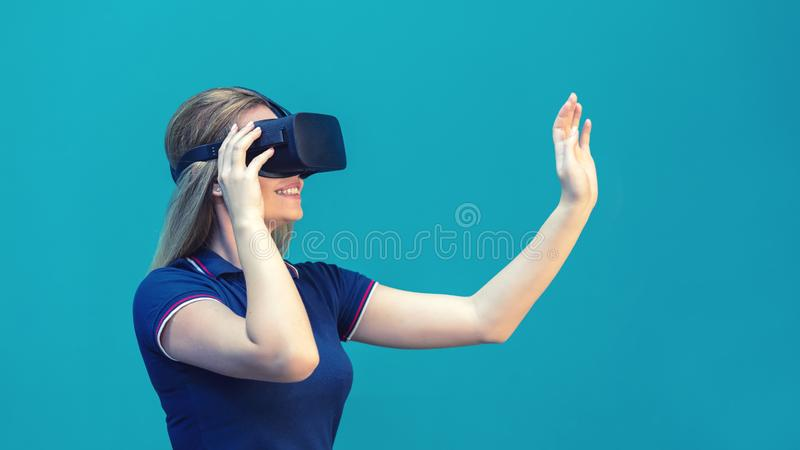 Happy young woman playing on VR glasses indoor. Virtual reality concept with young girl having fun with headset goggles royalty free stock photography