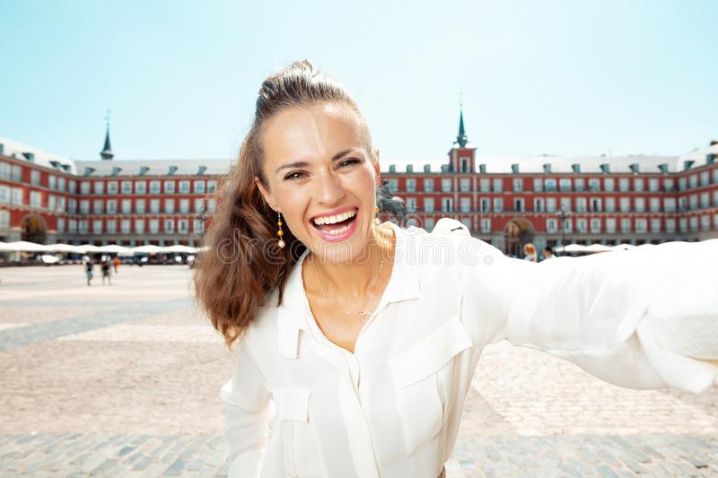 Happy young woman at Plaza Mayor in Madrid, Spain taking selfie. Happy young woman at Plaza Mayor taking selfie stock photography
