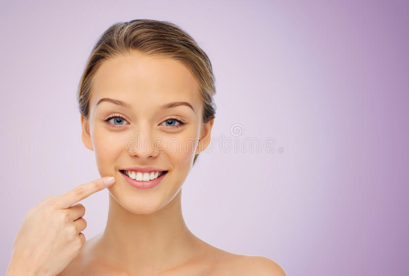 Happy young woman pointing finger to her smile stock photos