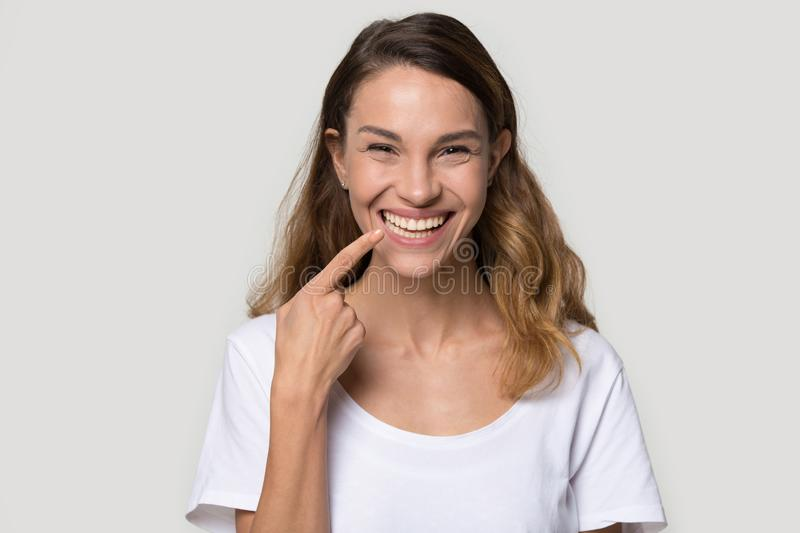 Happy young woman pointing finger at toothy healthy smile stock image