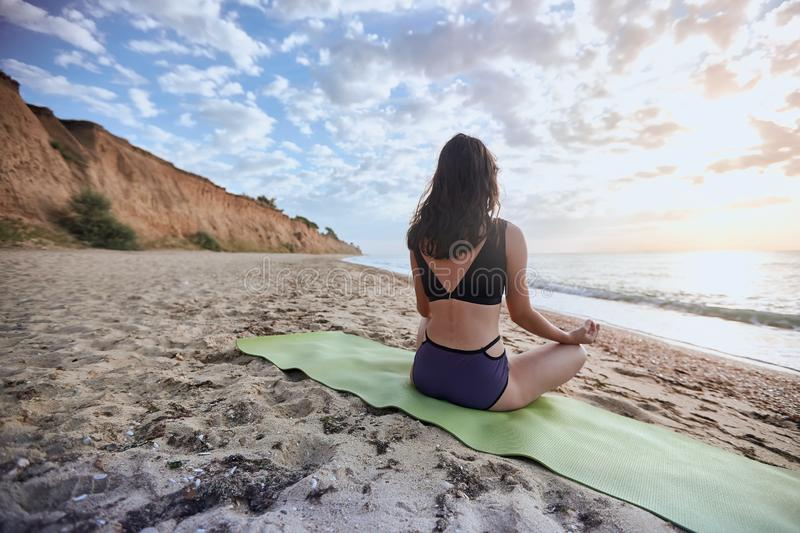 Happy young woman practices yoga and meditates in the lotus position on the beach royalty free stock image