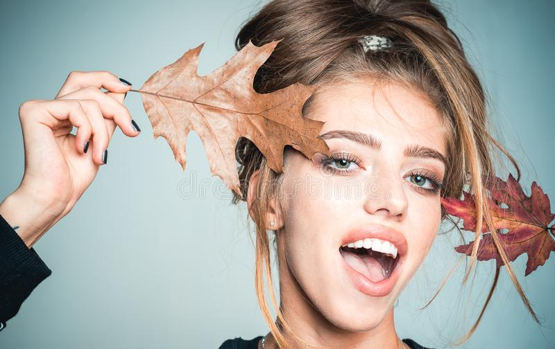 Happy young woman are preparing for autumn sale day. Surprise woman playing with leaf and looking at camera. Beautiful stock photo