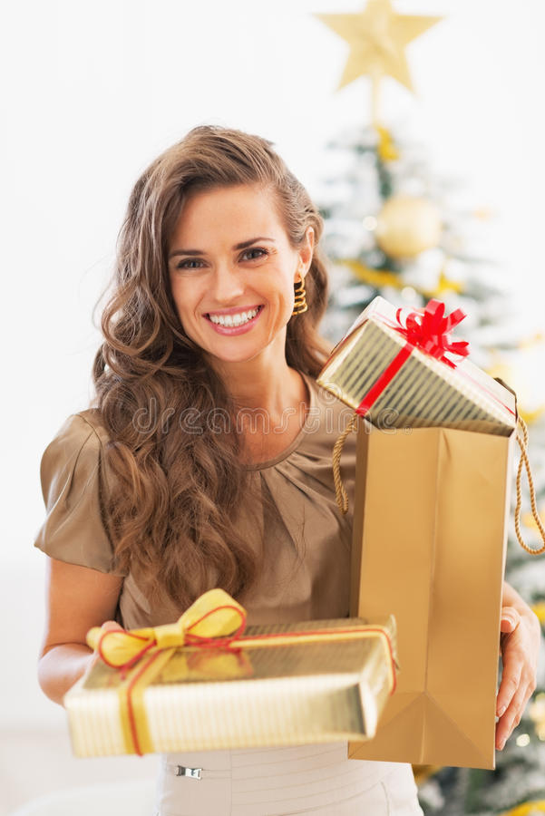Happy young woman present boxes in front of christmas tree stock images